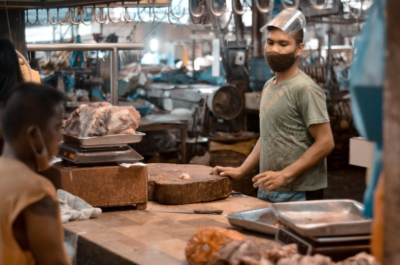 """THE BURGOS BUTCHER. A meat vendor tends to a buyer at the wet section of the Burgos Public Market in Bacolod City, Philippines on Monday, 12 October 2020, two days after the city government implemented a mass testing program."" by Rodney A. Jarder Jr., DNX News is licensed under CC BY-SA 2.0"