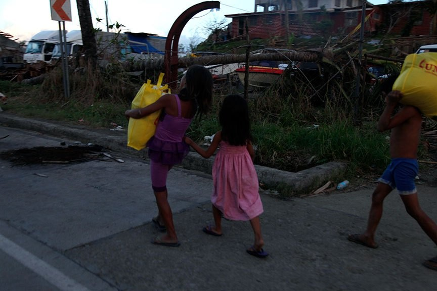CHILDREN head home after getting food packs from a government aid station in Tacloban City. | Photo by Julius D. Mariveles
