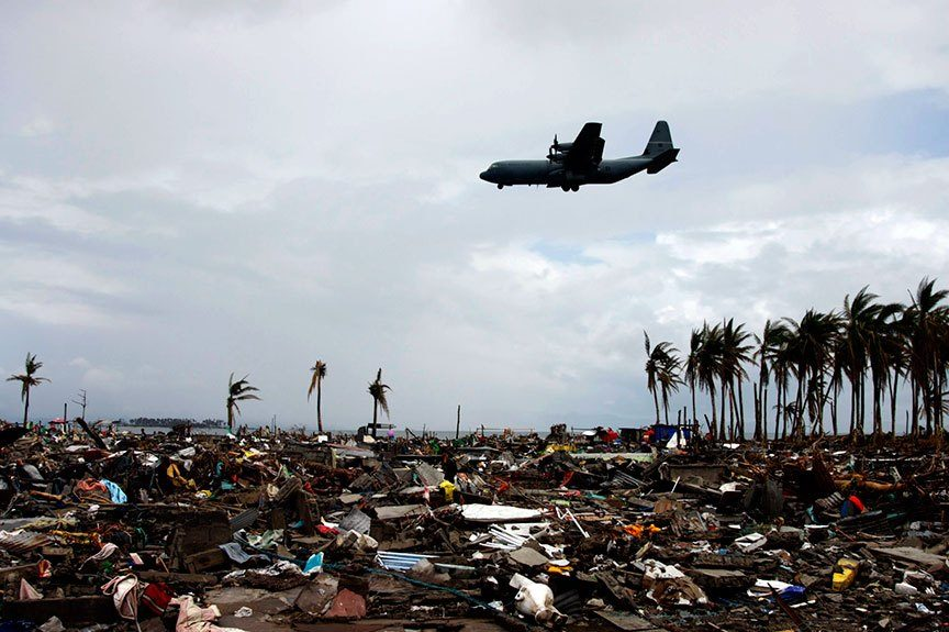 A C-130 cargo plane of the Royal Australian Air Force makes its final glide towards the runway of the Daniel Z. Romualdez Airport in Tacloban City, above the remains of  Fisherman's Village. It used to be a community of thousands. | Photo by Julius D. Mariveles