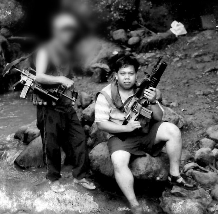 The author holds  an AR15 with a grenade launcher borrowed from the NPA as one of its Red fighters pose with him for posterity. | Photo from Julius Mariveles personal collection