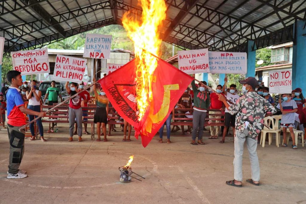 Residents of Sagay City and Toboso town burn flags of the Communist Party of the Philippines during an activity facilitated by the 79th Infantry Battalion to boost its counterinsurgency drive. | Photo by 79th Infantry Battalion